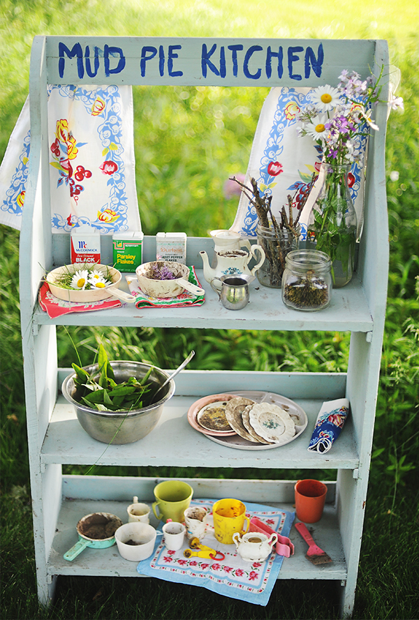 A kids outdoor play kitchen sits in a backyard